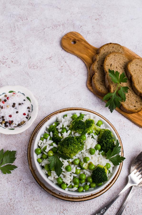 Crumbly white rice. With green vegetables in the dish on the table. Selective focus royalty free stock photo