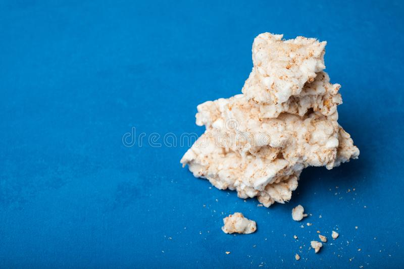 Crumbs and wreckage of dietary rice crispy snacks on a blue background, empty space for text royalty free stock image