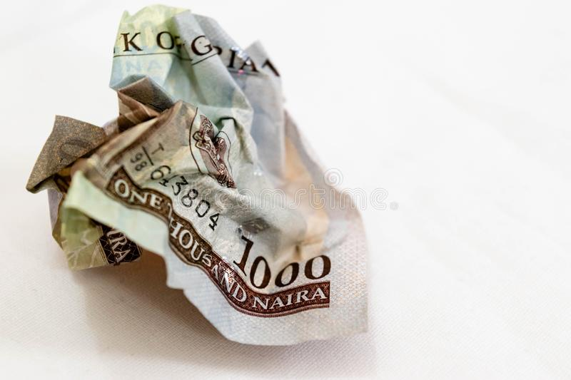 Crumpled banknote in a thousand Nigerian Naira on a White background for value depreciation and loss royalty free stock image