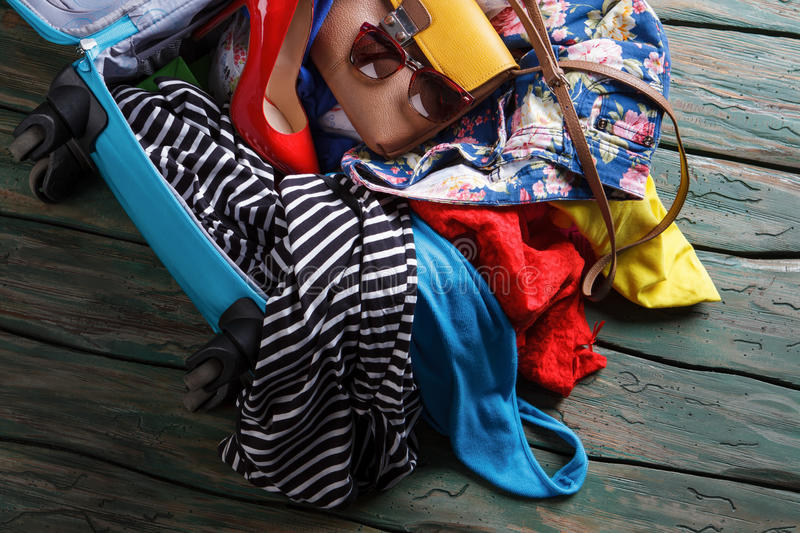 Crumpled clothes in blue suitcase. Heel shoe in opened bag. Trip will take a while. Just a few more things stock images