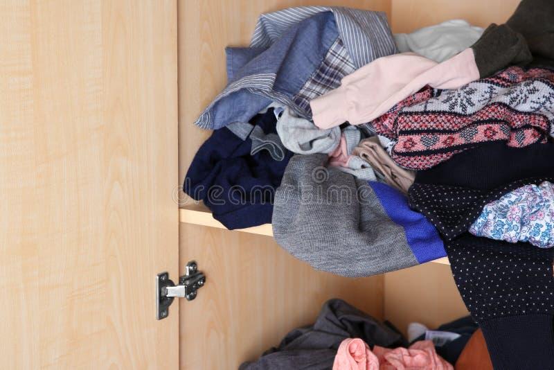 Crumpled clothes on wardrobe shelf,. Closeup stock photos