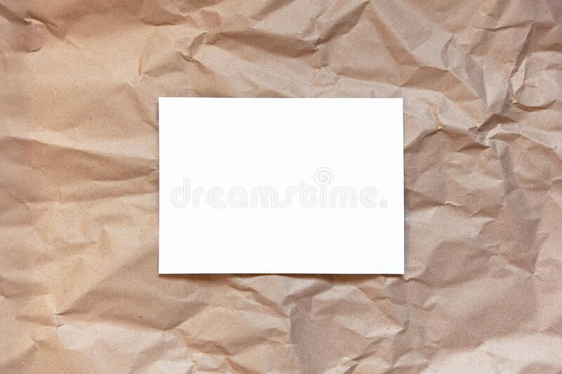 Crumpled craft brown paper background with white sheet in middle. Copy space. Horizontal. DIY, handicraft, back to school, ecology stock photography