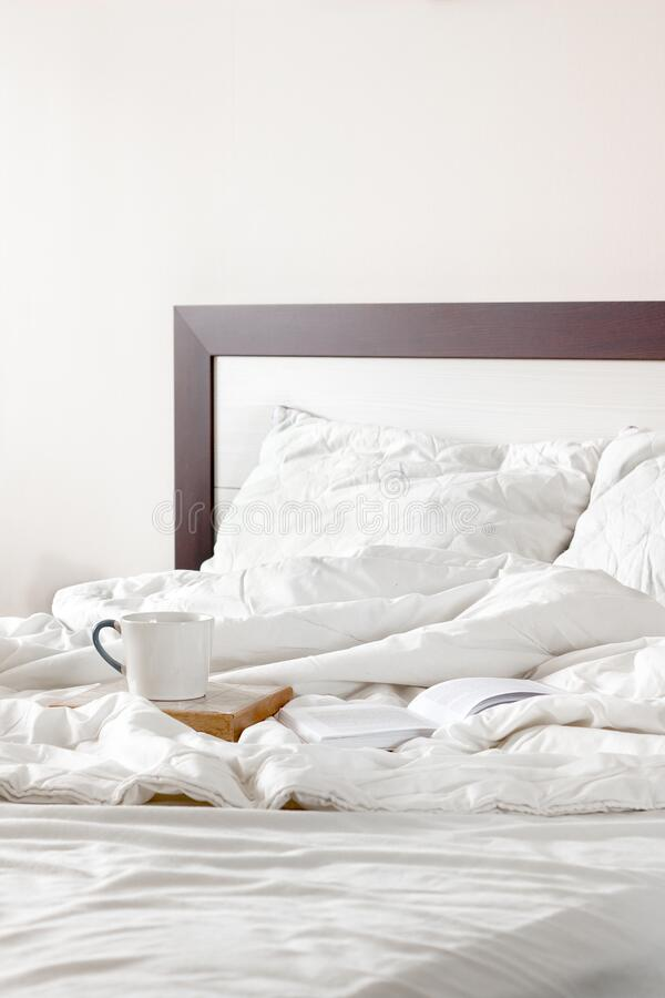 crumpled empty bed in the morning in bright sunny bedroom. coffee for breakfast and reading a book in bed royalty free stock photography