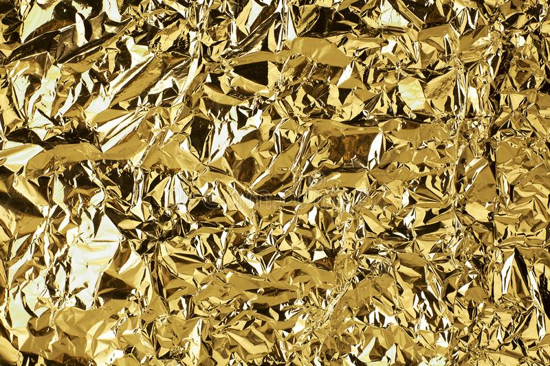 Crumpled golden foil shining texture background, bright shiny gold luxury design, metallic glitter surface stock images
