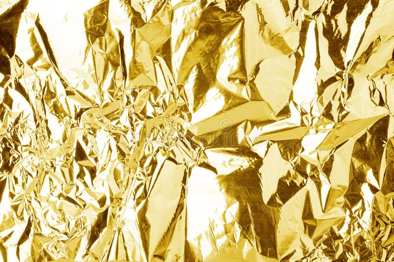Crumpled golden foil shining texture background, bright shiny gold luxury design, metallic glitter surface stock photography