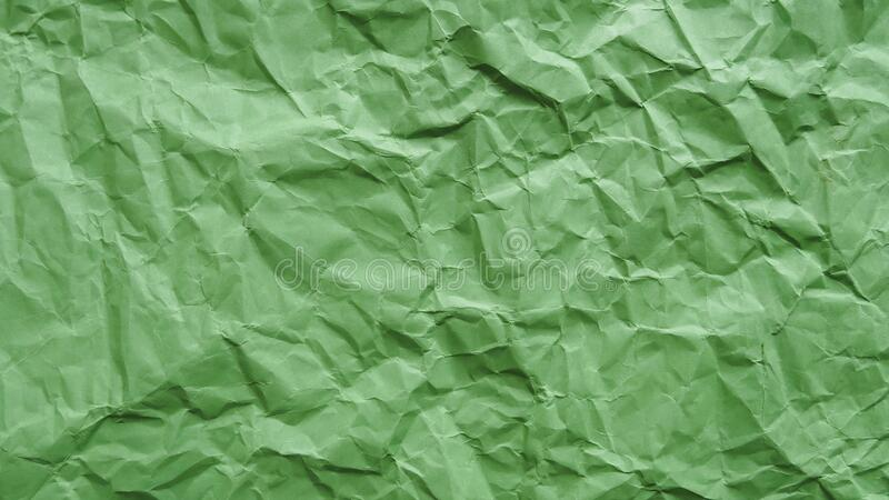 Crumpled green recycled paper, abstract background, copy space.  stock photo