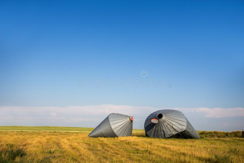 Crumpled metal grain storage bins damaged by wind stock images