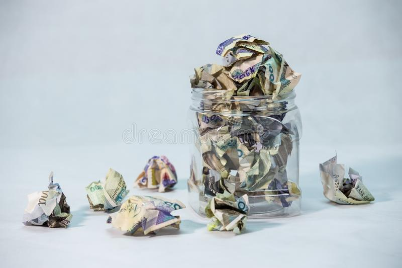 Crumpled naira notes in a bottle with white background. Depicting savings stock photography
