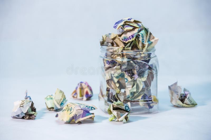 Crumpled naira notes in a glass jar concept of savings. Crumpled naira notes with white background royalty free stock photography