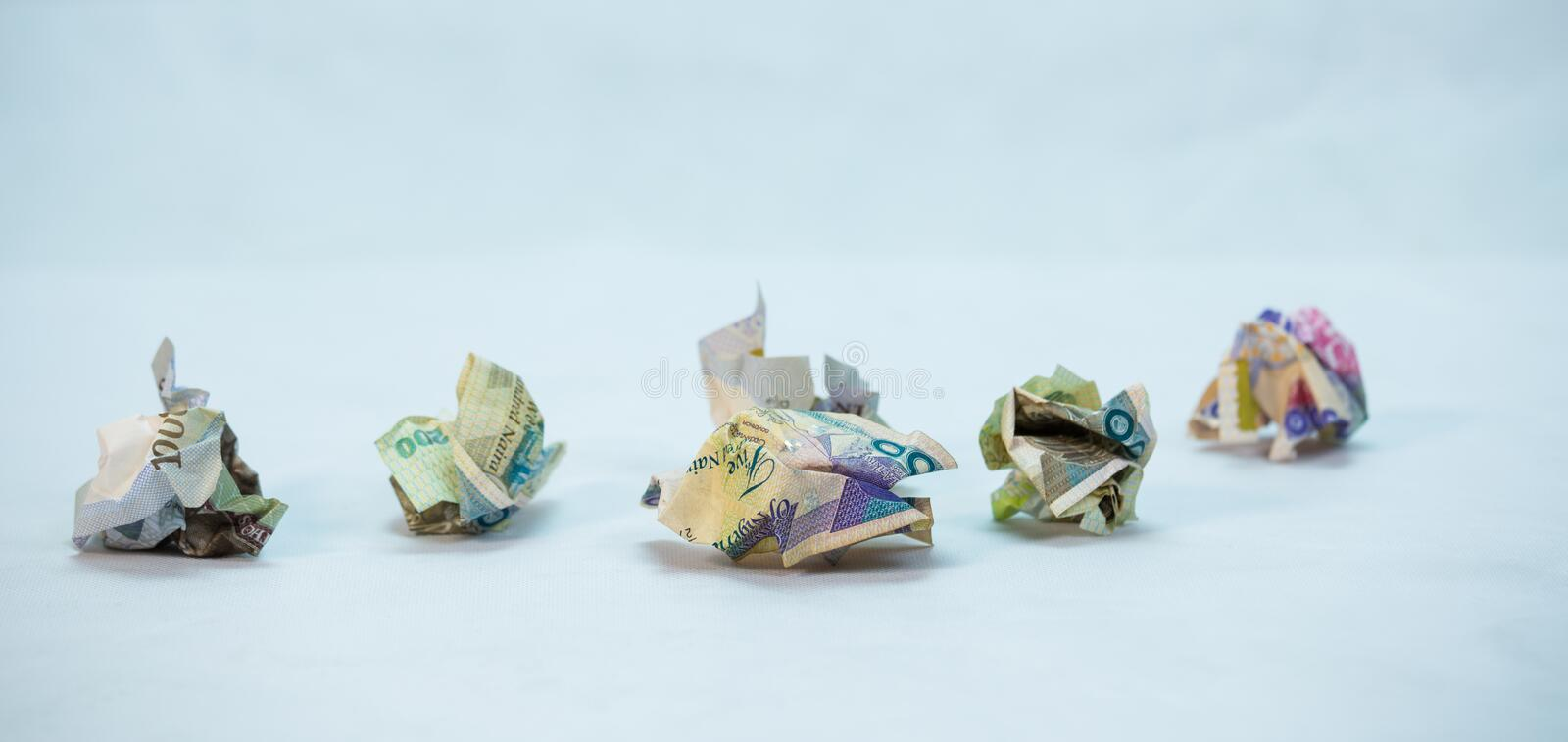 Crumpled naira notes in a glass jar concept of savings. Crumpled naira notes with white background royalty free stock photos