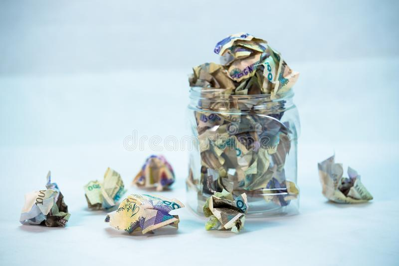 Crumpled naira notes in a glass jar concept of savings. Crumpled naira notes with white background royalty free stock images