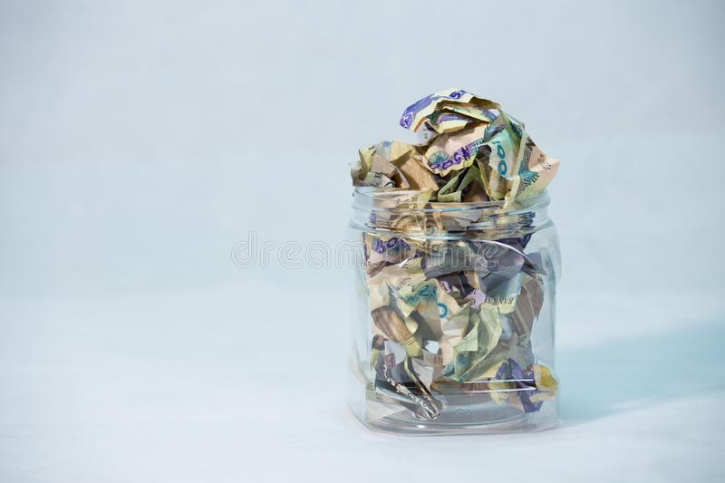 Crumpled naira notes in a glass jar concept of savings. Crumpled naira notes with white background stock images