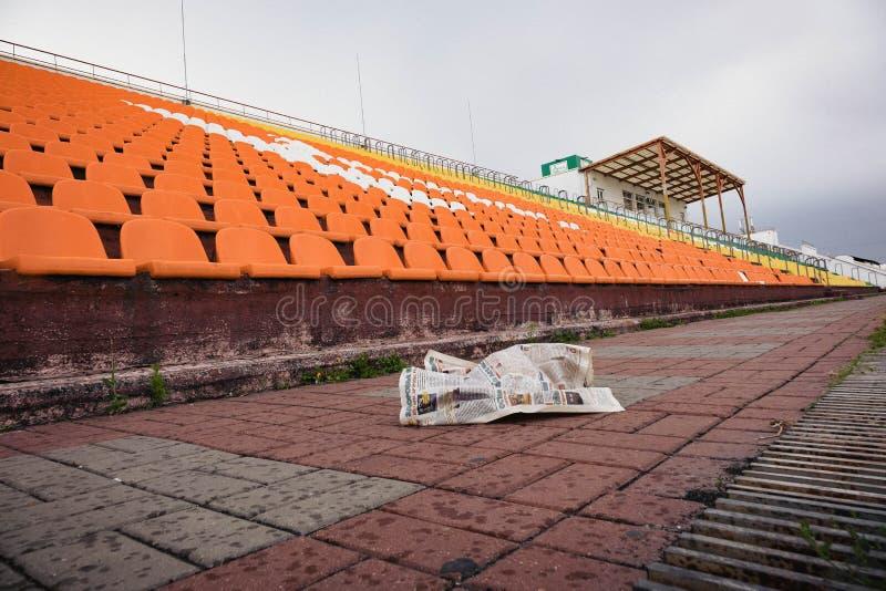 crumpled newspaper lying on the floor among the old abandoned stadium stock image