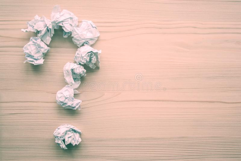Crumpled paper as brainstorming, creativity concept with place for text. Question mark folded from white crumpled paper balls on wooden background. Inspiration royalty free stock images