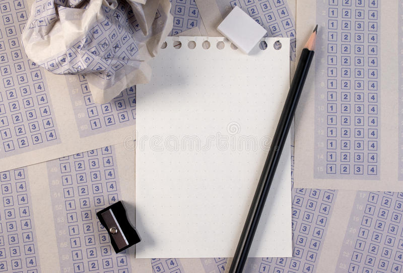 Crumpled paper ball of vintage classic answer sheet with pencil, sharpener and paper reduction. stock images