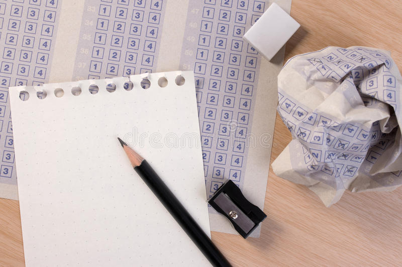 Crumpled paper ball of vintage classic answer sheet with pencil, sharpener and paper reduction. stock image