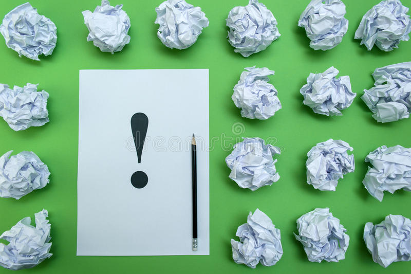 Crumpled paper balls and sheet of paper with exclamation mark stock photo