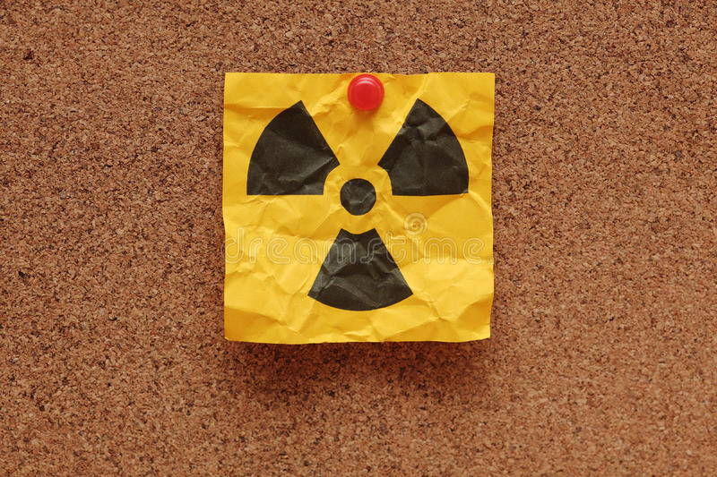 Crumpled Radioactive Sign. Crumpled adhesive note with Radioactive Sign on corkboard (bulletin board royalty free stock images