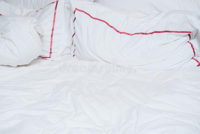 Crumpled white bed in early morning, red strips on pillows stock photography