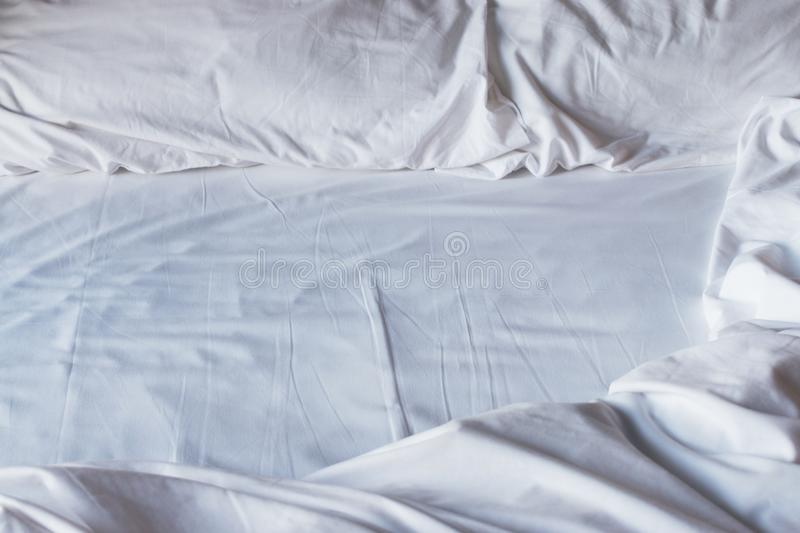Crumpled white bedclothes. Background. Sunny royalty free stock image