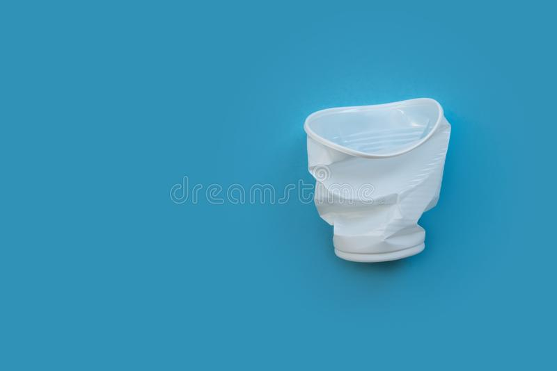 Crumpled white plastic cup on a blue background as a symbol of environmental pollution. royalty free stock photos