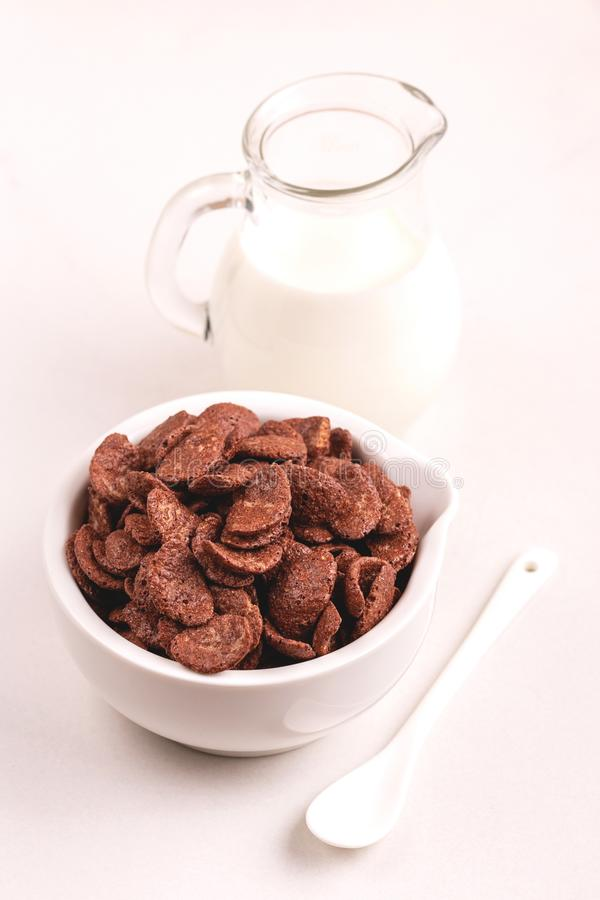Crunchy chocolate corn flakes in bowl with jar of milk royalty free stock photos