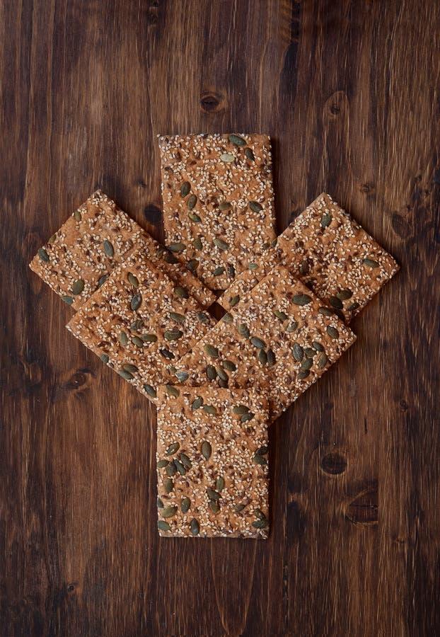 Ð¡runchy crispbread on a table. Crunchy crispbread on a wooden table. Healthy snack: cereal crunchy multigrain cereal flax seed pumpkin, coriander, sesame royalty free stock image