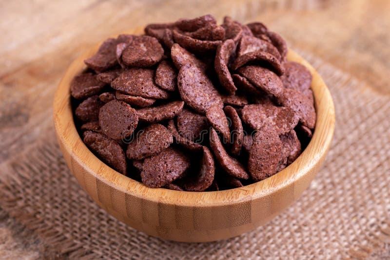 Crunchy czekoladowi kukurydzani płatki w drewnianym pucharze z burlap pieluchą zdjęcie stock