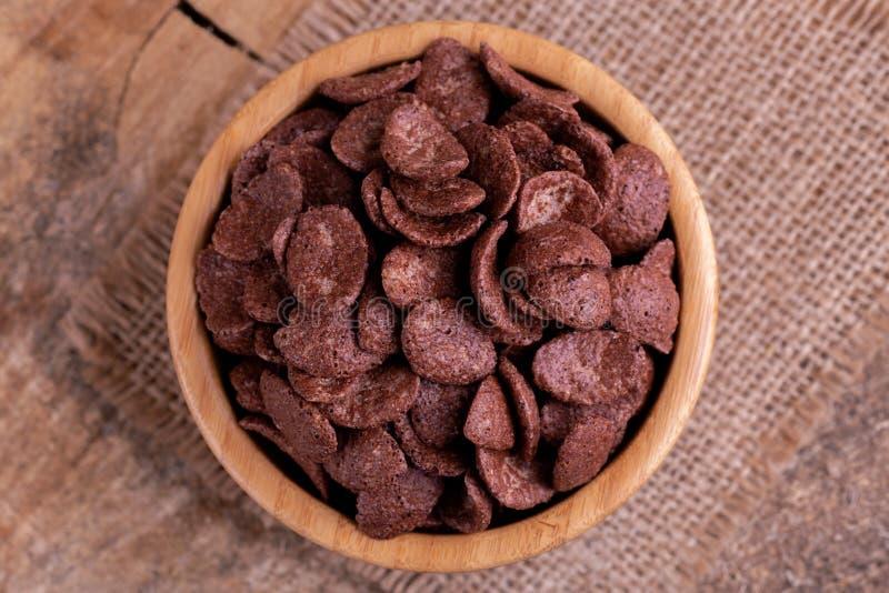 Crunchy czekoladowi kukurydzani płatki w drewnianym pucharze z burlap pieluchą fotografia royalty free