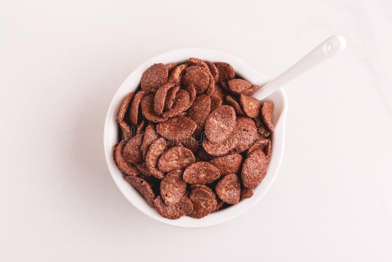 Crunchy czekoladowi kukurydzani płatki w pucharze na świetle wykładają marmurem tło obraz royalty free