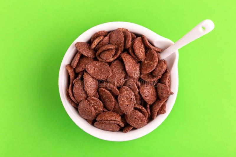 Crunchy czekoladowi kukurydzani płatki w pucharze na jaskrawym - zielony tło zdjęcia royalty free