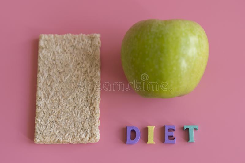 Crunchy loaves of bread and Apple the inscription diet on a pink background. Concept of losing weight and healthy lifestyle stock photo