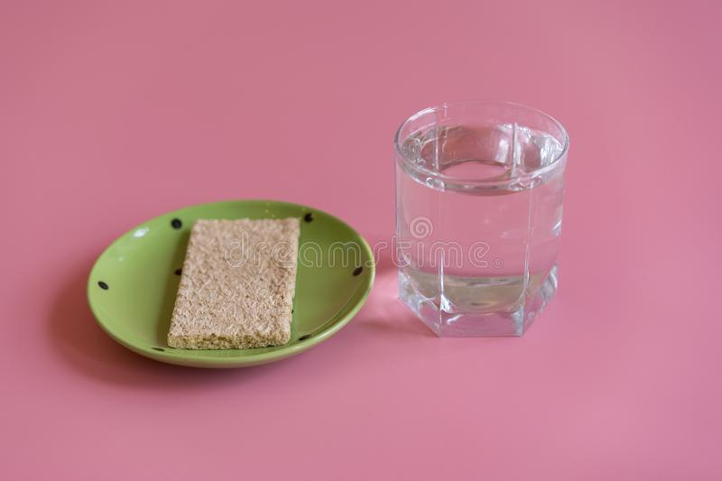 Crunchy loaves of bread and a glass of water. Concept of losing weight and healthy lifestyle.  royalty free stock photo