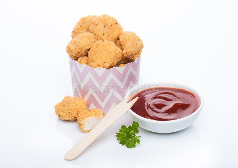 Crunchy pollo popcorn morde in bambini bicchieri di carta per pasti fast food su fondo bianco con forchetta di legno e ketchup fotografia stock