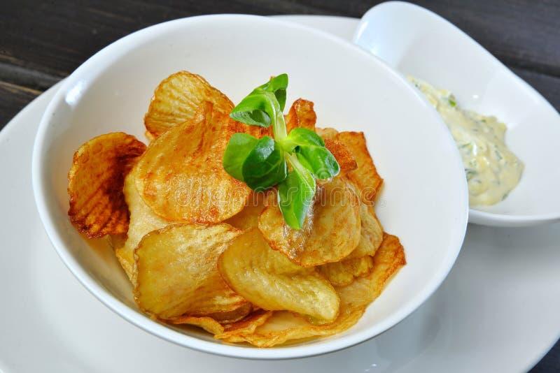 Crunchy potato crisps in bowl stock image