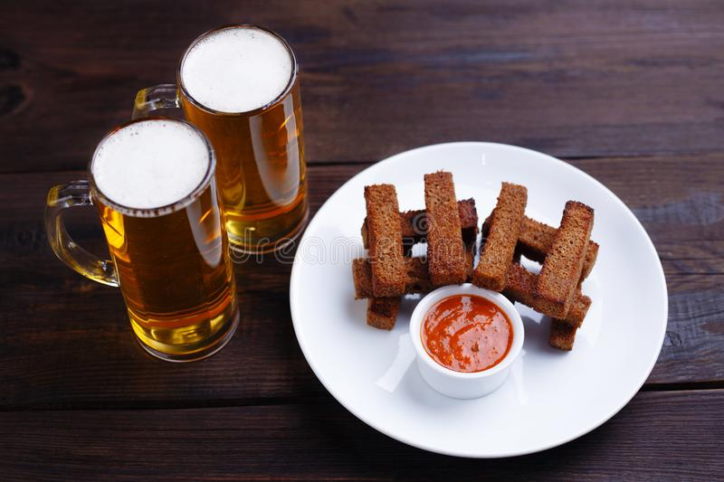 Crunchy rye toasts with sauce, popular beer snack. Popular pub snack for beer lovers and two mugs of lager, crunchy rye toasts with sauce stock image