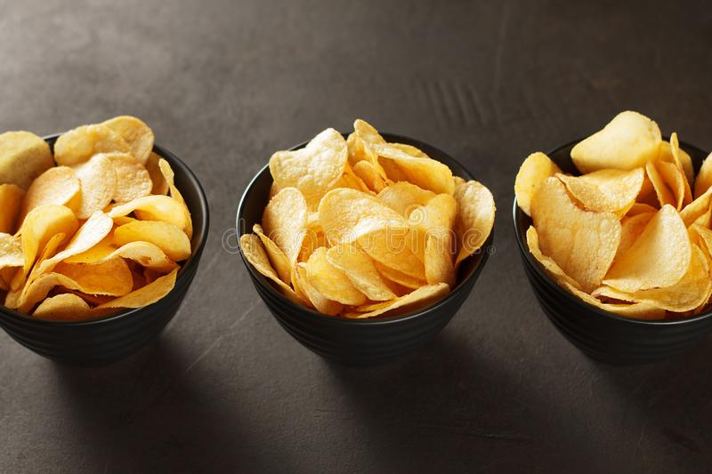 Crunchy snacks in three black bowl on dark brown background. stock photography
