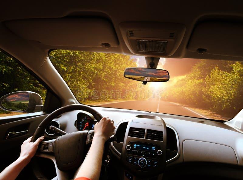 Cruscotto dell'automobile con le mani dell'autista sul volante e sugli specchietti retrovisori su una strada nel moto con gli alb immagine stock