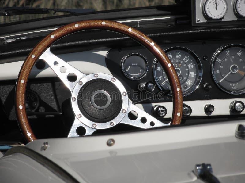 Cruscotto di vecchia automobile classica britannica Vista particolare del volante e del quadro portastrumenti del veicolo L'autom fotografia stock libera da diritti