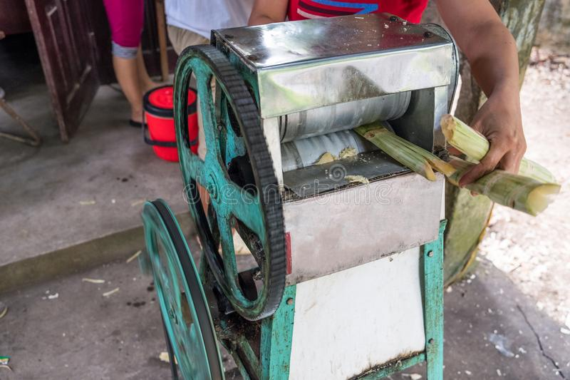 Crush machine working with crushed sugar cane in store royalty free stock photography