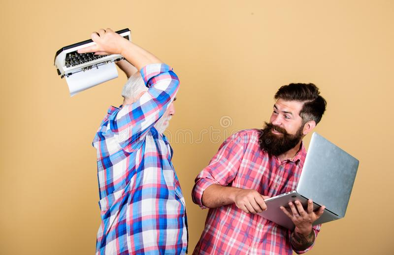 Crush test. retro typewriter vs laptop. New technology. father and son. family generation. youth vs old age. business royalty free stock photo