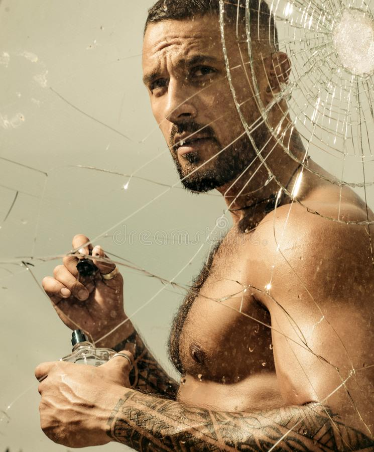 Crush test. theft. emotional discharge. bullet hole in glass. broken glass because of hit. destruction. headache concept. Sexy hispanic man broken mirror stock image