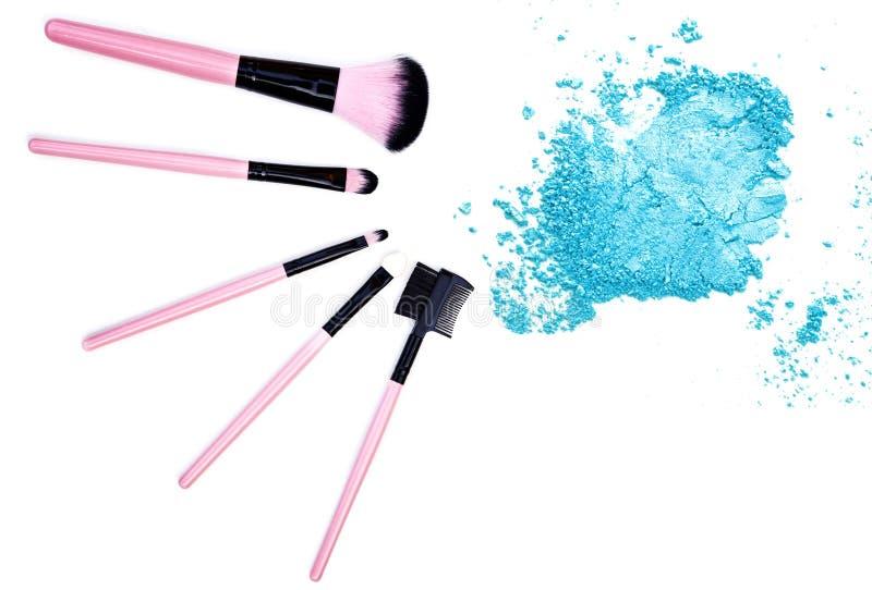 Crushed blue eyeshadow with makeup brush on white background. stock photo