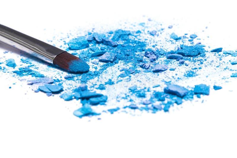 Crushed compact blue eyeshadow on white background stock images