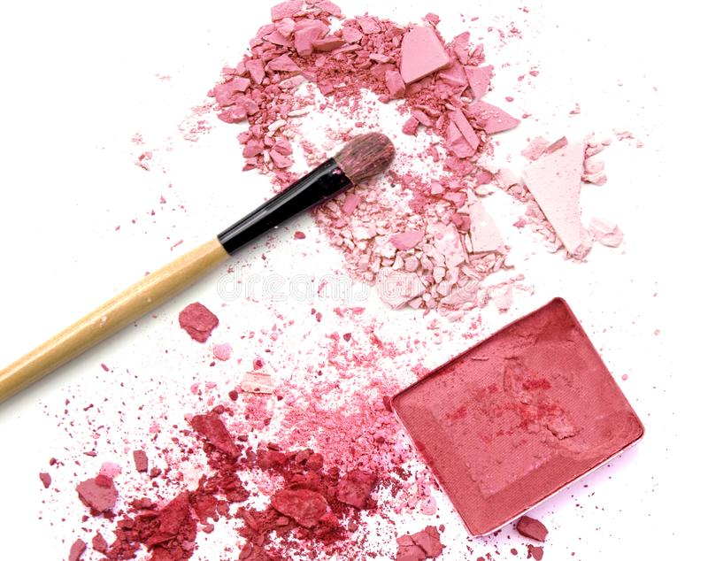 Crushed eye shadows with box and make up brush as a background. royalty free stock image