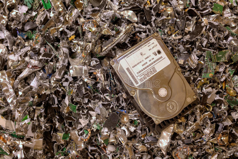 Crushed hard drives. A hard drive resting on a pile of shredded hard drives royalty free stock image