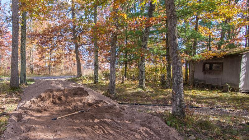 Crushed rock pile with shovel with rustic shed in background - rural road and walking path project in a beautiful colorful fall fo stock images