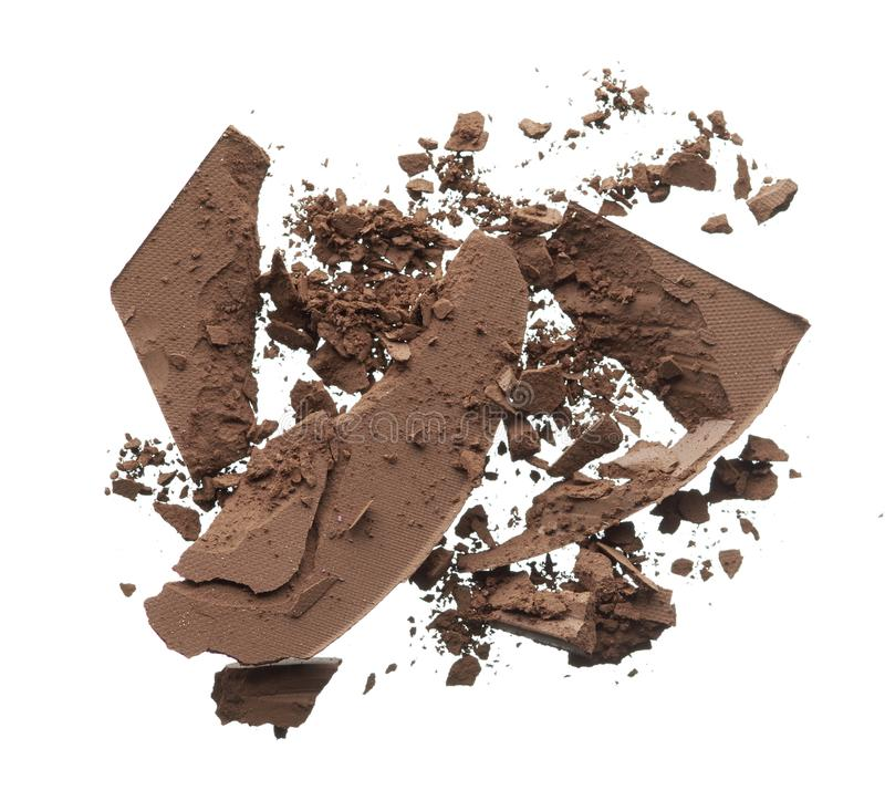 Crushed texture of dark brown eye shadow or powder. Crushed texture of dark brown eye shadow isolated on white background. Macro texture of broken chocolate royalty free stock photography