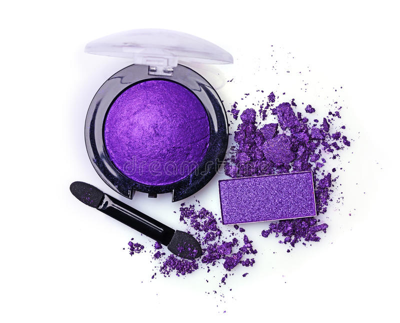 Crushed violet eyeshadow and applicator. Isolated on a white background stock photography