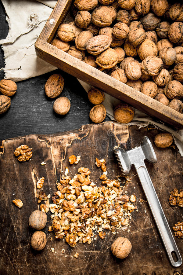 Crushed walnuts with a hammer on the old Board. stock photo